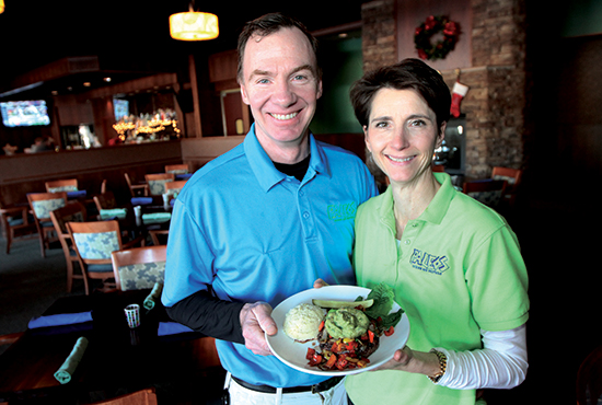 John and Elizabeth Pavlick, owners of recently-opened Paleos restaurant in Lino Lakes, have decided to give 10 percent of their December revenue to the Life Fund of the Archdiocese of St. Paul and Minneapolis. They are shown with one of their top menu items, the guacamole burger. Dave Hrbacek/The Catholic Spirit