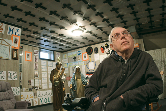 "Surrounded by more than 200 crosses on the walls and ceiling, Will Schafer sits in the basement of his Lakeville home, which he has labeled the ""Chapel of 200 Crosses and Hail Marys."" Dave Hrbacek/The Catholic Spirit"