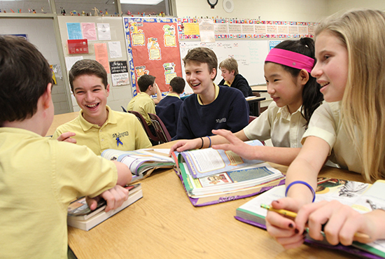 Sam Seitlinger, center, laughs during class with seventh-grade classmates Nicholas Bettenburg, left, Ethan Safi, Grace Creamer and Lucy Kulhanek.   Dave Hrbacek/The Catholic Spirit
