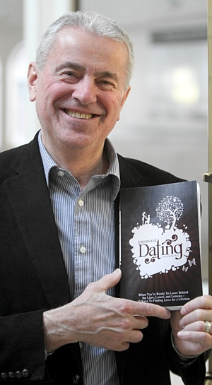 University of St. Thomas psychology professor John Buri holds a copy of his book about dating. Dave Hrbacek/The Catholic Spirit