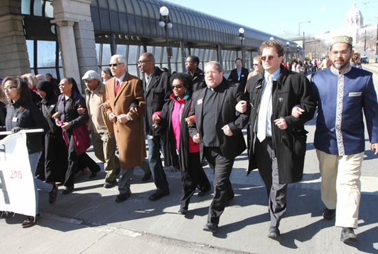 Father Erich Rutten, third from right, chair of the Archdiocesan Commission for Ecumenical and Interreligious Affairs, participates in an event March 8 commemorating the 50th anniversary of the civil rights march in Selma, Ala. led by Martin Luther King Jr. Local religious leaders joined him, including Steve Hunegs, second from right, executive director of the Jewish Community Relations Council, and Asad Zaman of the Muslim American Society of Minnesota. More than 1,000 people marched from the State Capitol to Central Presbyterian Church in downtown St. Paul. Speakers, including Father Rutten, delivered remarks at the church following the march. Dave Hrbacek/The Catholic Spirit