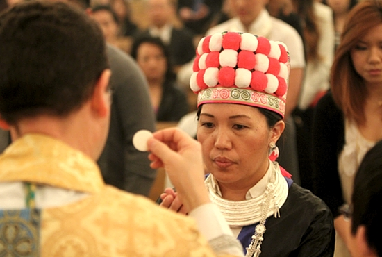Choua Yang receives Communion from Bishop Andrew Cozzens during Easter Sunday Mass April 5 at St. Vincent de Paul in St. Paul. The Mass also featured a celebration of the 20th anniversary of the Hmong presence at St. Vincent, which prompted Yang and others to come dressed in traditional Hmong attire. Dave Hrbacek/The Catholic Spirit