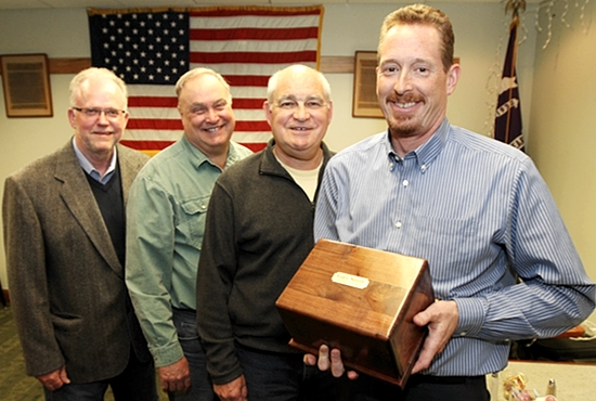 From left, volunteers Greg Eaton of St. Thomas Becket in Eagan, Paul Stoll, Mike Flynn of St. Cecilia in St. Paul and John Bromen of St. John Neumann in Eagan pose with the cremated remains of Gary Smith, a homeless man whom they befriended before he died of a heart attack Jan. 15. Not pictured is Steve Hawkins of St. John Neumann, who helped organize the volunteers to do a memorial service for Smith. Dave Hrbacek/The Catholic Spirit