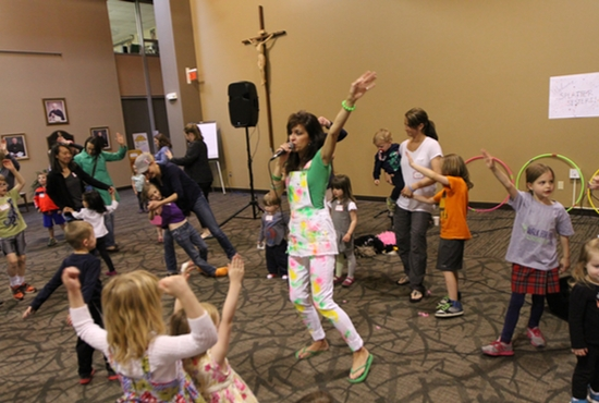 Baibi Vegners, a parishioner of Pax Christi in Eden Prairie and a longtime member of the Splatter Sisters trio, sings and dances with the children and their parents who attended their April 28 show. The act turns 25 this year, and is engaging a new generation of kids. Dave Hrbacek/The Catholic Spirit