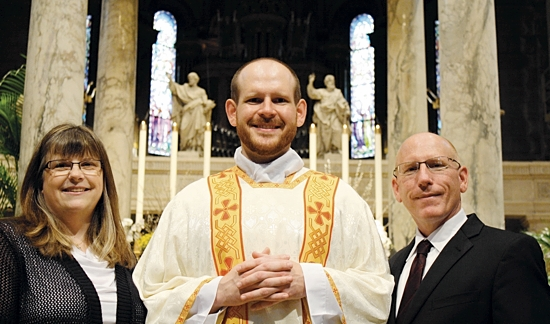 Lori and Tom McKenzie pose with their son, Deacon T.J. McKenzie, upon his ordination to the transitional diaconate in May 2014. He'll be ordained a priest for the archdiocese with six other men May 30 at the Cathedral of St. Paul.  Photo courtesy of the McKenzies