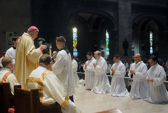 Archbishop John Nienstedt of St. Paul and Minneapolis prays during a May 2 Mass at the Basilica of St. Mary in Minneapolis where nine men were ordained deacons. Kneeling, from left, are deacons Matthew Northenscold, Mark Pavlak, Adam Tokashiki, Vaughn Treco and Joseph Zabinski. Not pictured are deacons Neil Bakker, Michael Daly, Kyle Kowalczyk and Michael McClellan.