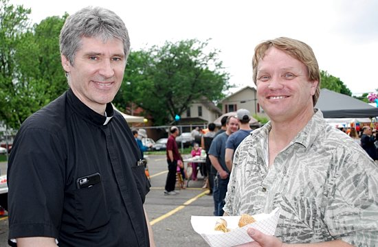 Father Michael Becker and John Tolo attend the Hmong Summer Festival hosted by St. Vincent de Paul in St. Paul. Father Becker and Tolo have led its evangelization efforts in the Frogtown neighborhood. Bridget Ryder/For The Catholic Spirit