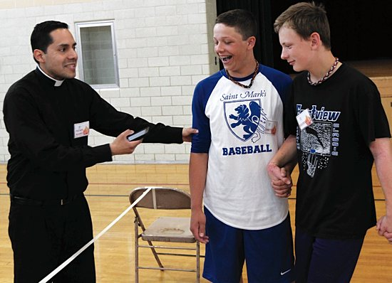 Father Alvaro Perez helps eighth-graders Bennett Theisen, center, and Roderick MacDonald play a game.