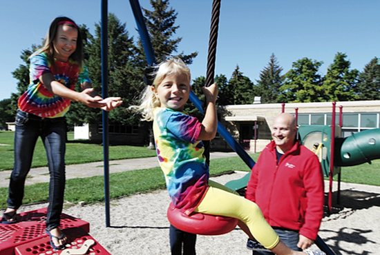 Bella Bemmels, 4, gets a push from her sister, Halle, 12, on the zipline at St. Anne's School in Le Sueur as their dad, Principal Adam Bemmels, observes. Halle, entering public middle school, attended St. Anne, Bella will attend the school's prekindergarten program, and their sister, Gabby, 8, will be in third grade at the school. The girls are wearing their St. Anne tie-dye shirts. Dave Hrbacek/The Catholic Spirit