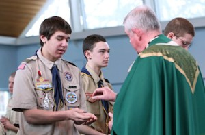 Life Scout Daniel Pelis receives Communion from Msgr. Robert Thelen during a Feb. Mass at Holy Cross Church in Nesconset, N.Y., to marking Scout Sunday. This year Scout Sunday coincided with the 105th anniversary of the founding of the Boy Scouts of America. (CNS photo/Gregory A. Shemitz)