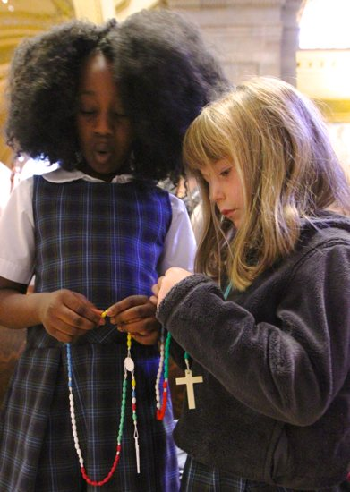 From left, second-grader Jazmine Sombai and kindergartner Lizzy Churchill pray during the Children's Rosary Pilgrimage Oct. 7 at the Cathedral of St. Paul in St. Paul. Catholic schools from across the Archdiocese of St. Paul and Minneapolis gathered for the annual event. Dave Hrbacek/The Catholic Spirit