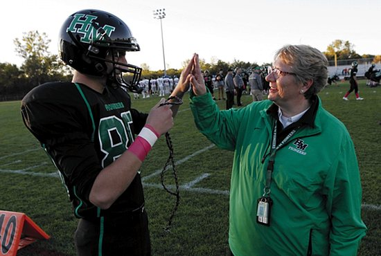 "Benedictine Sister Linda Soler gives a high five to Hill-Murray senior Garrett Kaelin before a game against Simley Oct. 2. Kaelin, a kicker, is holding Sister Linda's ""football rosary,"" which she carries with her while walking the field before games to cheer on and pray with the players. Dave Hrbacek/ The Catholic Spirit"