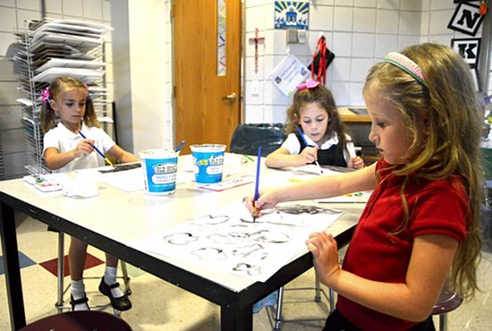 "At St. Joseph Catholic School in Waconia, first-graders, from left, Mary-Margaret Donovan, Soleil Ehalt and Venice Lonnes are learning about colors and developing creativity as they use watercolors to illustrate their personal interpretation of ""God's rainbows,"" noted teacher Mollie Olsen. Bob Zyskowski/The Catholic Spirit"