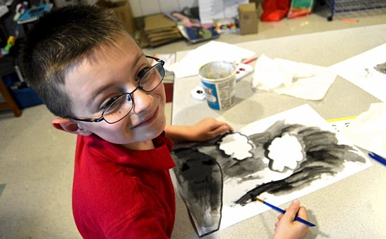 "First-grader Jared Templin works on the clouds and the threatening sky portion of his watercolor painting of ""God's rainbow"" at St. Joseph Catholic School in Waconia. The activity combines learning about colors with developing students' creativity, teacher Mollie Olsen explained. Bob Zyskowski/The Catholic Spirit"