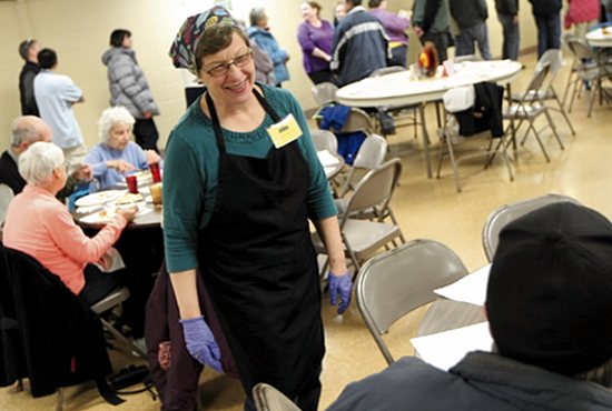 Pat Haas takes time out from serving the meal and supervising volunteers to greet guests at the weekly Thursday night dinner Nov. 19 at Mary, Mother of the Church in Burnsville. Dave Hrbacek/The Catholic Spirit