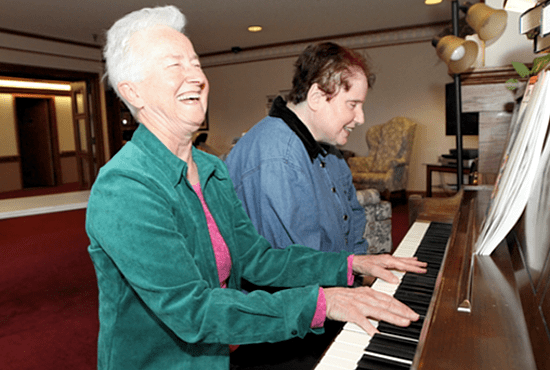 Living Word Sister Mary Nicholas Eiden, left, plays piano and sings with Martha Lambert, a resident of Castle Ridge in Eden Prairie, a care center of Presbyterian Homes and Services. Dave Hrbacek/The Catholic Spirit