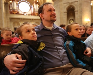 Joe Vandermark, center, of Our Lady of the Prairie in Belle Plaine sits with his twin sons, Alex, left, and Zach at the annual Prayer Service for Life at the Cathedral of St. Paul in St. Paul Jan. 22. Dave Hrbacek/The Catholic Spirit