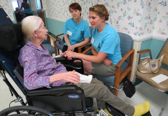 Stacey Jackson, front center, a graduate of Seton School in Manassas, Va., and Amy Endres speak with nursing home resident Kathleen Grace in early July during this summer's pilot of SALT, a mission program hosted by the Carmelite Sisters for the Aged and Infirm. CNS photo/courtesy Carmelite Sisters for the Aged and Infirm
