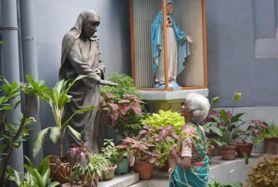 With folded hands, Margeret Rose stood praying near Blessed Teresa's statue near the entrance of the headquarters of the Missionaries of Charity.