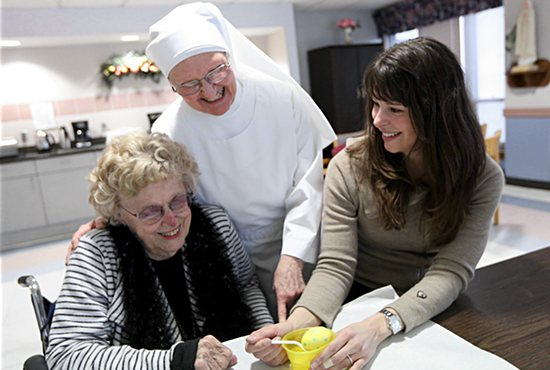 Linda Sitko, right, of the Cathedral of St. Paul in St. Paul, dyes Easter eggs at the Little Sisters of the Poor Holy Family Residence in St. Paul with resident Eleanor Matczynski, left, and Sister Amy Kaiser during a day of service March 23. Dave Hrbacek/The Catholic Spirit