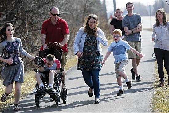 From left front, Maggie Thibault runs to a local park with Stas (in stroller), Dan, personal care attendant Brittany Wiitala and Ricky. Back left: Chuck Thibault (holding Susha), Bobby and Gretchen.