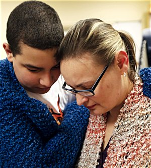Veronica Rosa and her 12-year-old son, parishioners of St. John the Baptist in Savage, share a moment after receiving prayer shawls during a session of PALS March 3.