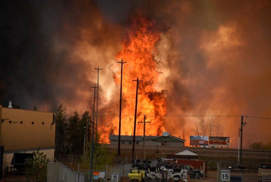 Flames from a wildfire rise in an industrial area of Fort McMurray, Alberta, May 4. The entire city has been evacuated because of the wildfire. CNS photo/courtesy CBC News via Reuters