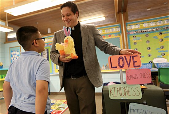 Father Aaron Meszaros uses props including a stuffed chicken and a suitcase covered with placards to teach important spiritual lessons to second-grader Travis Nguyen and other students at St. Alphonsus School in Brooklyn Center. Dave Hrbacek/The Catholic Spirit