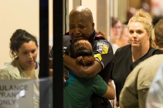A Dallas police officer is comforted July 7 at Baylor University Hospital's emergency room entrance after a shooting attack. Snipers shot and killed five police officers and wounded seven more at a demonstration in Dallas to protest the police killing of black men in Baton Rouge, La., and a suburb of Minneapolis. Two civilians also were injured in Dallas. CNS photo/Ting Shen, The Dallas Morning News handout via Reuters