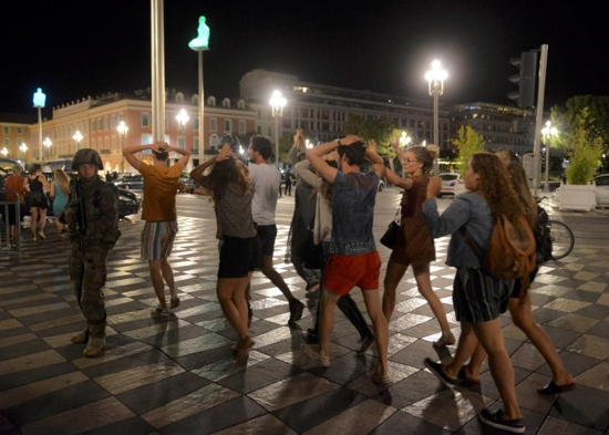 People cross the street with their hands on their heads as a French soldier secures the area July 15 after at least 84 people were killed along the Promenade des Anglais in Nice, France, when a truck ran into a crowd celebrating the Bastille Day national holiday July 14. CNS photo/Jean-Pierre Amet, Reuters