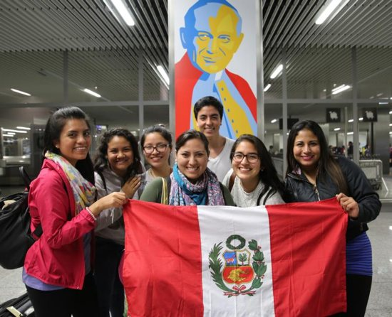 World Youth Day pilgrims from Lima, Peru, pose for a photo in front of an image of St. John Paul II after arriving July 23 at John Paul II International Airport in Krakow, Poland. CNS photo/Bob Roller
