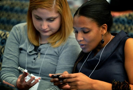 Young women tweet messages during a 2012 conference in Washington. Low-cost video messaging carried across increasingly video-friendly social media platforms will define this year's World Youth Day experience in Krakow, Poland, say several organizations. CNS photo/Paul Jeffrey)