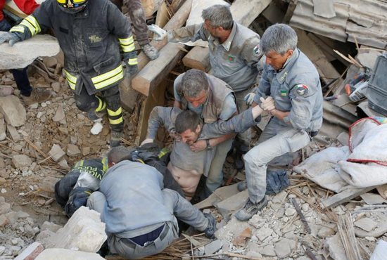 A man is rescued from the ruins following an earthquake in Amatrice, Italy, Aug. 24. CNS photo/Remo Casilli, Reuters