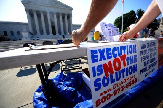 A member of the Abolition Action Committee hangs a sign in front of the Supreme Court in Washington during a 2008 vigil to abolish the death penalty. CNS photo/Shawn Thew, EPA