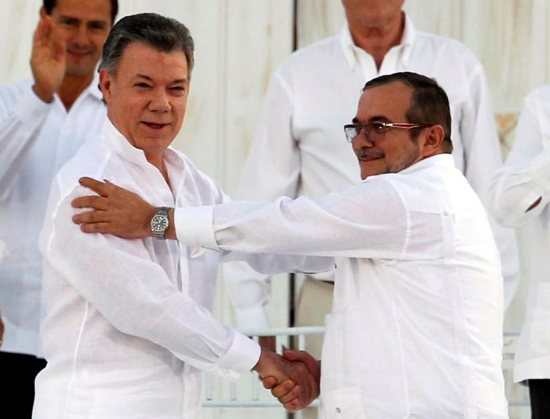 Colombian President Juan Manuel Santos and Marxist rebel leader Rodrigo Londono Echeverri of FARC, the Revolutionary Armed Forces of Colombia, shake hands Sept. 26 in Bogota after signing an agreement to end Latin America's last armed conflict. Santos has been awarded the 2016 Nobel Peace Prize. CNS photo/John Vizcaino, Reuters