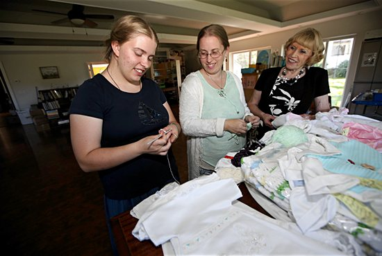 Christelle Hagen, center, works on baby clothing with her daughter, Emilie-Rose, left, and mother Marilyn Kallio. Dave Hrbacek/The Catholic Spirit