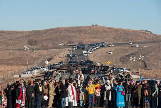 Clergy of many faiths from across the United States participate in a prayer circle Nov. 3 in front of a bridge in Standing Rock, N.D., where demonstrators confront police during a protest of the Dakota Access pipeline. Demonstrations against the pipeline are taking place on the Standing Rock Indian Reservation near Cannonball, N.D. CNS photo/Stephanie Keith, Reuters