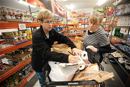 From left, volunteers Sheri Gahl and Cinda Dorholt assemble a food order at Westonka Food Shelf in Mound Nov. 22. The food shelf is housed in the newly constructed Grace Family Center next door to Our Lady of the Lake in Mound. Gahl is a parishioner at OLL. Dave Hrbacek/The Catholic Spirit