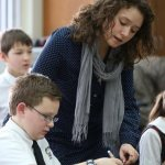 Sister teaches younger brother at Holy Family Academy