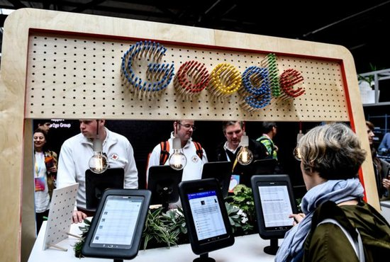 Visitors look at the digital media offerings at the booth of technology giant Google at the Republica 17 digital conference