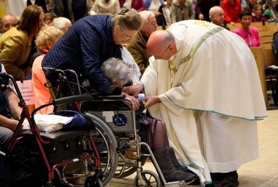 A priest blesses an elderly woman in 2017 at the Knock Shrine in Ireland.