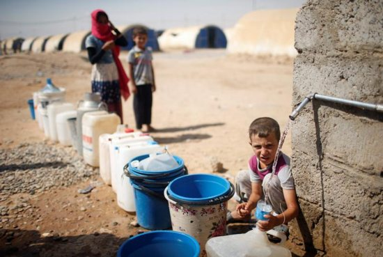 A displaced Iraqi boy fills a bottle with water in Jada, Iraq