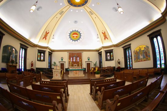 """The renovation of Our Lady of Lourdes in Minneapolis features rich oak accents and a light """"Marian blue"""" ceiling."""
