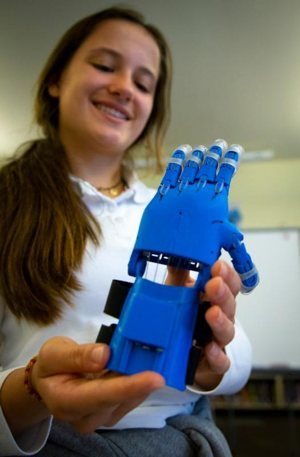 Rosali Patterson, a rising eighth-grade student at St. John Fisher Catholic School in Portland, Ore., tests out the prosthetic hand she helped design and produce for underprivileged children