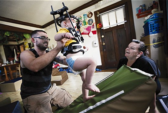 Kayden Peltier does some exploring in the living room with help from his parents, Kyle and Nicolle