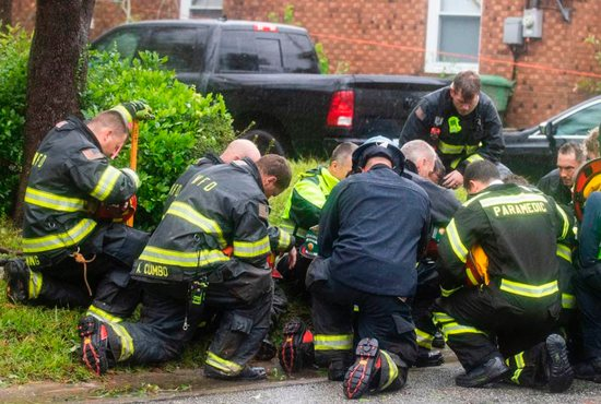 Firefighters pray after attempting to remove a giant tree that toppled onto a house and killed two people and injured a third Sept. 14 when Hurricane Florence came ashore in Wilmington, N.C. The powerful storm is poised to affect more than 10 million people in the southeastern U.S.