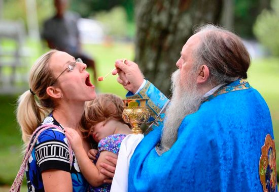 Father John Szada, chaplain of the Carmel of Jesus, Mary and Joseph in Elysburg, Pa., distributes Communion during pilgrimage at Assumption of the Blessed Virgin Mary Ukrainian Catholic Church