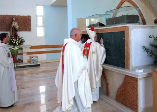 "Bishop Petru Gherghel of Iasi, Romania, blesses the tomb of Veronica Antal Sept. 23, the day she was beatified in Nisiporesti, Romania. The 22-year-old was beatified as a ""martyr to chastity,"" six decades after she was murdered while resisting rape."