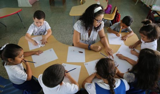 Maria Santiago works with her prekindergarten students in 2017 at Good Heart of Mary Catholic School in San Juan, Puerto Rico