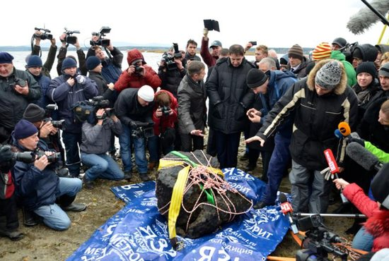 Journalists gather around a piece of a meteorite, according to local authorities and scientists, after it was pulled from the bottom of Russia's Chebarkul Lake in 2013.